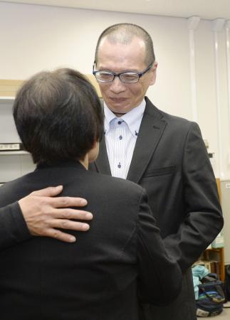 大分刑務所から釈放され、母親(手前)と再会する朴龍晧さん=26日夜、大阪市の司法記者クラブ