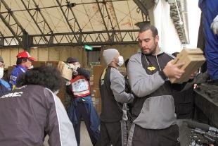 (写真:釜石駅隣のシープラザ釜石にて物資の積み降ろしのボランティアに参加する選手たち。)