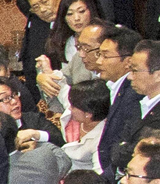 自民党の大沼瑞穂参院議員(写真中央白のスーツ)に手をかける民主党の津田弥太郎参院議員(写真中央、大沼氏の真上のグレーのスーツ)。大沼氏はこの後、写真右手奥までひきずられ、膝の上に乗せられた後に引き倒さ