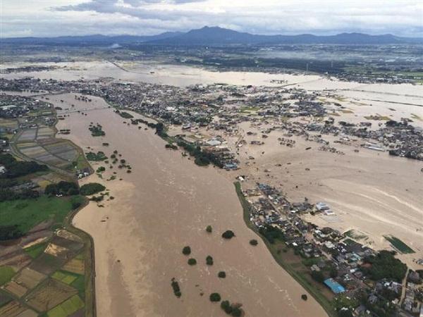 大雨で鬼怒川(左)の堤防が決壊し、住宅地に流れ込む大量の濁流 =10日午後4時20分、茨城県常総市(本社チャーターヘリから、大山文兄撮影)