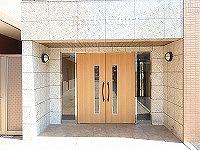 木目調の扉がオシャレな間口の広いエントランス入口
