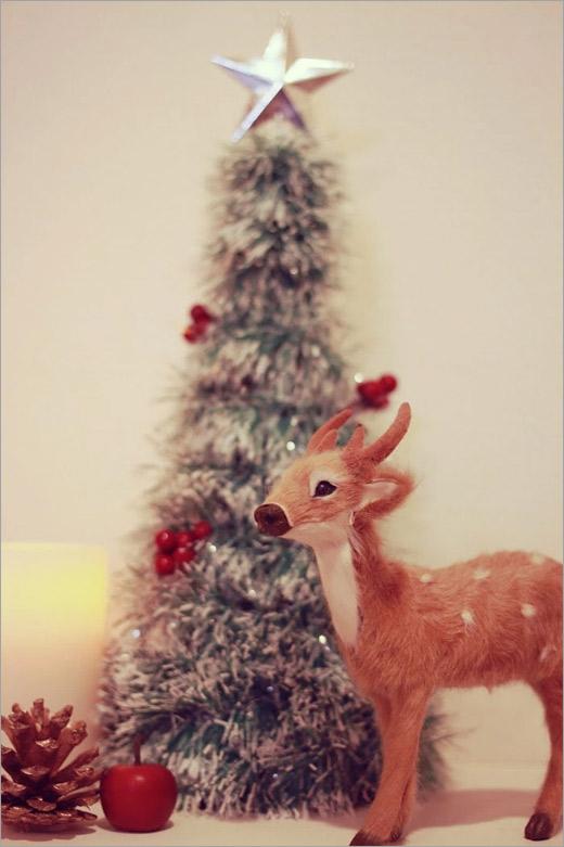 クリスマスツリーの前でトナカイぶってる子鹿くん