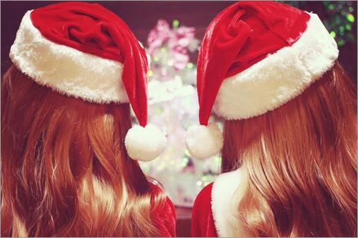クリスマスパーティーでサンタ帽を寄せ合う双子のサンタクロース